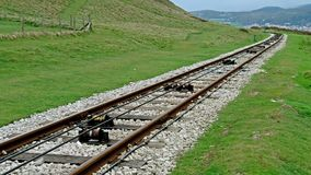 Close view of tram rail tracks showing the cable system which pulls the trams. Up to the Great Orme Mountain in LLandudno, Wales stock video footage