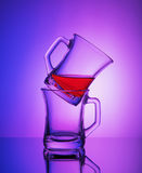 Close view of two empty crystal cups with the rest of tea on the gradient blue and purple background stock photography