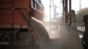 10 September, 2016, Mariupol, Ukraine, Ukrtransagro LLC. Close view of unloading grain trucks at elevator on elevating. Close view of unloading grain trucks at stock video