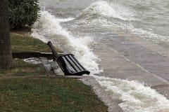Close view of water splashing on a sitting bench near a lake shore stock image