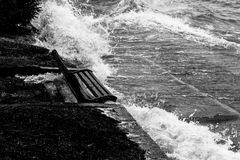 Close view of water splashing on a sitting bench near a lake sho Stock Image