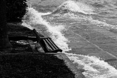 Close view of water splashing on a sitting bench near a lake sho Stock Photography