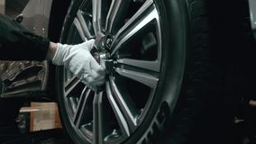 Close view of the wheel of sport car with red brake caliper.nAluminum Rim and mechanic hand in white gloves. Close view of the wheel of sport car with red brake stock footage
