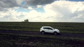 Close view white car drives along road in dark cloud shadow stock footage