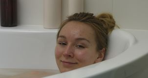 Relaxing in bath. The close view of woman in bath. She is resting in bathtube. The camera is focus on her face and then move on to left stock footage
