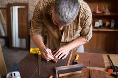A joiner using his chisel. Close view of a wood carpenter using the chisel. A craftsman at his table, carving from the wood royalty free stock image