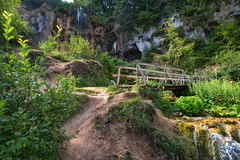 Close view of wooden bridge over stream with waterfall. Stock Photos
