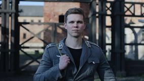 A portrait of a young handsome German soldier raising his head. A concentration camp reconstruction on the background stock footage