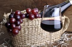 Close on wineglass for tasting. Close on a wineglass in front of grapes on a basket to serve wine with bottle on a rustic wooden background Stock Photo