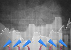 Female hands in a row holding blue paper trumpets against graphs background Royalty Free Stock Image