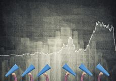 Female hands in a row holding blue paper trumpets against graphs background Stock Image