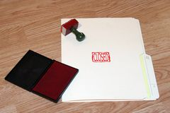 Closed. Office series with stamp and pad on desk with file folder stock photography