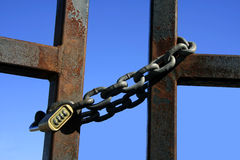 Closed. Iron chain with safety number lock closing a rusty gate Royalty Free Stock Photo