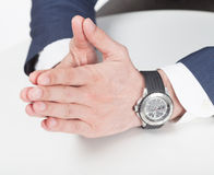 Closed arms. Mens hands in suit and hand watch showing closed arms on the white table Royalty Free Stock Photography
