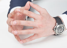 Closed arms. Mens hands in suit and hand watch showing closed arms on the white table Stock Images