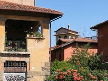 A closed balcony in the district Garbatella in Rome in an old building with other villas around. Blue clear sky. Sunny day. Tree with flowers in foreground Stock Photo