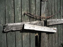 Closed Barn Door. An old broken, weathered barn door with a chain Stock Images