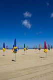 Closed beach umbrellas. Waiting for the tourists in a sunny morning, in Deaville, France Royalty Free Stock Image