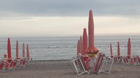Closed beach umbrellas on the beach in the evening. Clip stock footage