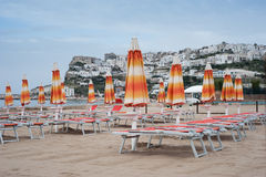 Closed beach umbrellas and deck chairs on an empty beach Stock Image