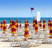 The closed beach umbrellas and red flag Stock Images