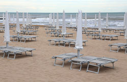 closed beach umbrellas and sun loungers on the sandy beach in wi Stock Photography