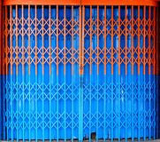 Bi-color retractable folding metallic gate. Closed bi-color retractable folding metallic gate in front of traditional shop Royalty Free Stock Images