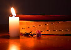 Closed Bible by candle light. Lying on a wooden table with small flower Stock Photos