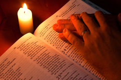 Closed Bible by candle light. Bible by candle light with hands resting on it Stock Photography