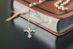 A closed bible is set on a table with a rosary draped on it. Royalty Free Stock Photo