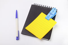 Closed black cover notebook ,yellow empty post note and pen. Closed black cover notebook ,yellow empty post note, pen and blue clip with white background Royalty Free Stock Photography