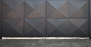 Closed black metal gate with square pattern stock image