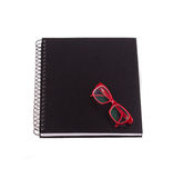 Closed black spiral notebook, glasses with red rim on top. Royalty Free Stock Photo