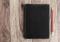 Closed black spiral notebook and pencil on wooden desk Stock Image