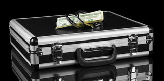 Closed black suitcase with dollars and handcuffs Stock Images