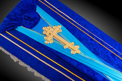 Closed blue coffin covered with cloth  on gray background. coffin close-up with gold Church cross. Stock Photos