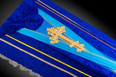 Closed blue coffin covered with cloth isolated on gray background. coffin close-up with gold Church cross. Royalty Free Stock Photos