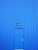 Closed blue door. In blue wall Royalty Free Stock Image