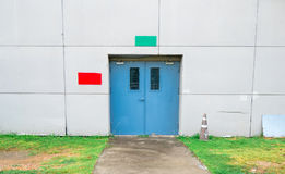 Closed blue door with green and red text box on white concrete wall, grass and walkway. With copy space Royalty Free Stock Photo
