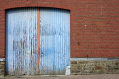 Closed blue door of an old farm with peeling varnish Stock Photo