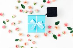 Closed blue gift box with pink roses on a white background. Closed blue gift box with pink roses on white background in flat lay style. Top view Royalty Free Stock Photo