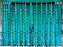 Closed retractable folding metallic gate. Closed blue/green retractable folding metallic gate in front of traditional shop Royalty Free Stock Photography