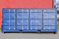 Closed blue standard cargo container. Stands in port area, side doors face Royalty Free Stock Photography