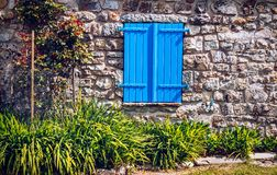 Closed blue window blinds at stone house.  Stock Image