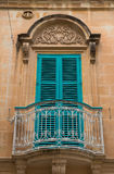 Closed blue window shutters and a small balcony. In Malta Royalty Free Stock Image