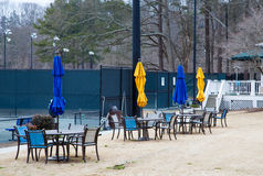 Closed Blue and Yellow Umbrellas at Tennis Court Stock Photo