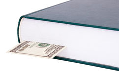 Closed book with a bookmark $ 100 on the right. Closed book with a dark green cover closeup. bank note is $ 100 as a bookmark in a book. Objects isolated on a Stock Images