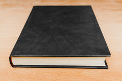 Closed book with empty black leather cover Stock Photography