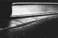 A closed book with a Golden edge on an old black wooden table with copy space. Black and white photo Royalty Free Stock Image