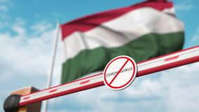 Closed boom gate with STOP CORONAVIRUS sign on the Hungarian flag background. Quarantine in Hungary